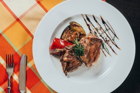 top view of grilled chicken with vegetables on plate on table napkin