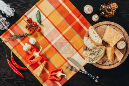 top view of table napkin with vegetables and cutting board with parmesan cheese on table