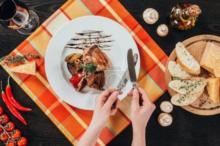 cropped image of woman sharpening knives above grilled chicken