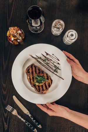 image recadrée de femme mettant assiette avec steak de boeuf sur la table