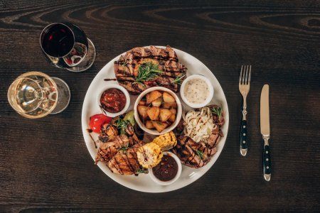 Photo for Top view of plate with beef steaks, chicken wings and wine on wooden table - Royalty Free Image