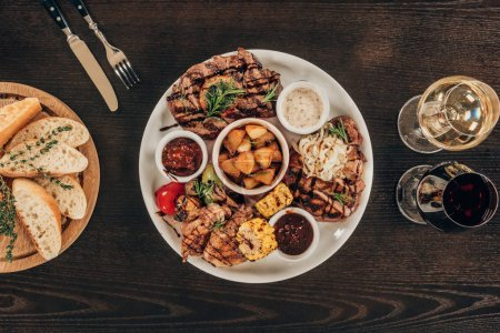 top view of plate with beef steaks, chicken wings and wine with bread on wooden table