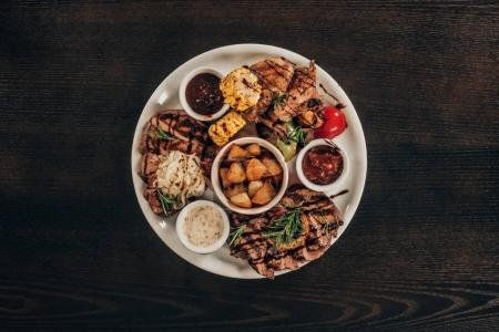 top view of plate with beef steaks, chicken wings and grilled vegetables on wooden table