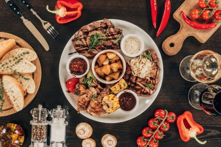 top view of plate with beef steaks, grilled vegetables and wine on table