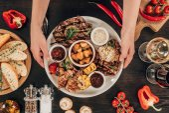 """Постер, картина, фотообои """"обрезанное изображение женщины положить плиты с говяжьи стейки, куриные крылышки и приготовленные на гриле овощи на столе"""""""