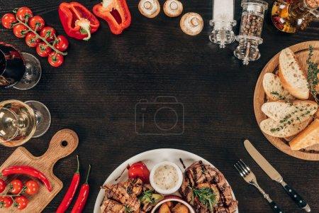 Photo pour Vue de dessus des légumes frais, steaks de boeuf cuit et vin sur table - image libre de droit