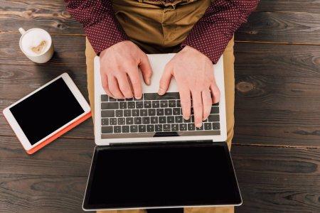 Photo pour Vue du dessus de l'homme d'affaires assis tablette numérique, tasse de café et ordinateur portable avec écran blanc - image libre de droit