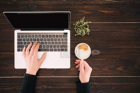 Photo for Cropped view of woman hands on laptop with blank screen and coffee cup - Royalty Free Image