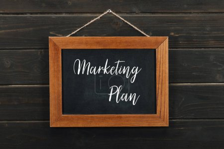 Board with lettering marketing plan hanging on wooden wall