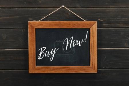 Photo pour Conseil avec lettrage acheter maintenant accroché sur un mur en bois - image libre de droit