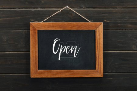 Board with lettering open hanging on wooden wall