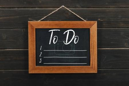 Photo for Board with lettering to do hanging on wooden wall - Royalty Free Image
