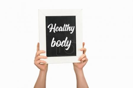 Cropped image of woman hands holding board with lettering healthy body isolated on white