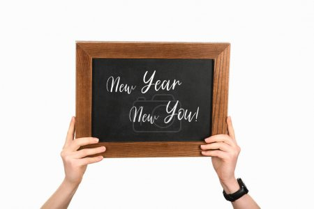 Cropped view of woman hands holding board with lettering new year new you isolated on white