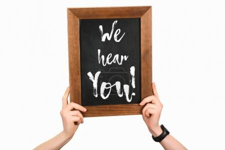 Cropped image of woman hands holding board with lettering we hear you isolated on white