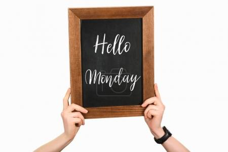 Cropped image of woman hands holding chalkboard with lettering hello monday isolated on white