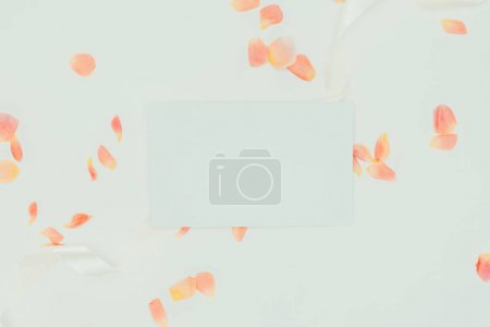 Photo for Top view of beautiful tender rose petals with ribbon and blank card on grey - Royalty Free Image