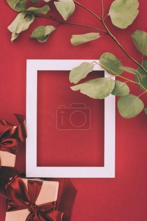top view of empty white frame, gift boxes and twig with green leaves on red