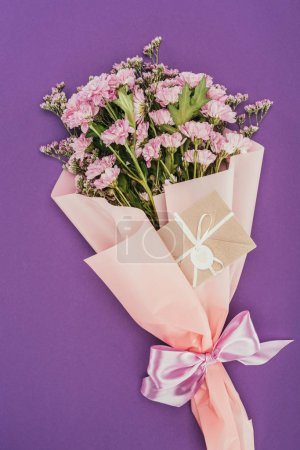 bouquet of beautiful pink flowers and decorative envelope on violet