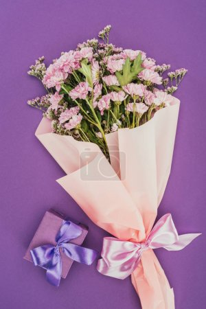 bouquet of beautiful pink flowers and gift box on violet
