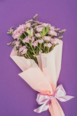 beautiful floral bouquet with pink ribbon on violet