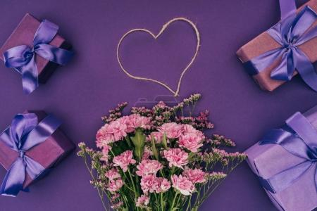 Photo for Bouquet of beautiful pink flowers, heart-shaped rope and gift boxes on violet - Royalty Free Image