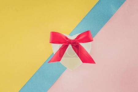 Photo for Top view of white heart shaped gift with pink ribbon on colorful background - Royalty Free Image