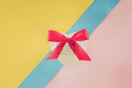 Photo pour Vue du dessus du cadeau en forme de coeur blanc avec ruban rose sur fond coloré - image libre de droit