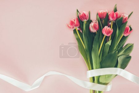 bouquet of beautiful pink tulips with green leaves and ribbon on pink