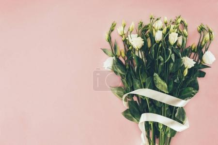 bouquet of beautiful white flowers with green leaves and ribbon on pink