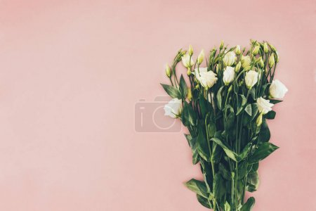 bouquet of beautiful white eustoma flowers with green leaves on pink