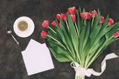 top view of beautiful red tulips, cup of coffee and blank envelope with greeting card