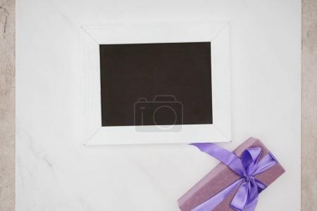 top view of blank chalkboard with gift box on white