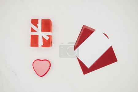 top view of opened red envelope with blank paper and gift boxes isolated on white