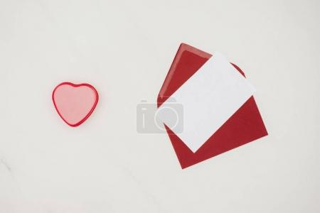 top view of red envelope with blank paper and heart shaped box isolated on white