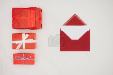 top view of red envelope with blank paper and row of gift boxes isolated on white