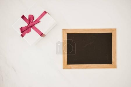 top view of blank blackboard in frame with gift box isolated on white