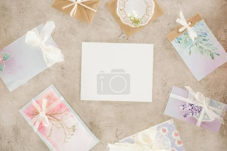 top view of blank paper surrounded with greeting cards on concrete surface