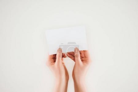 cropped shot of woman holding blank paper in hands isolated on white