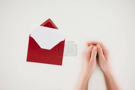 cropped shot of woman holding hands near opened red envelope with blank paper isolated on white
