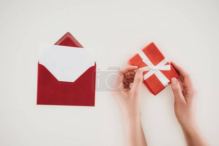 cropped shot of woman opening gift box with red envelope isolated on white