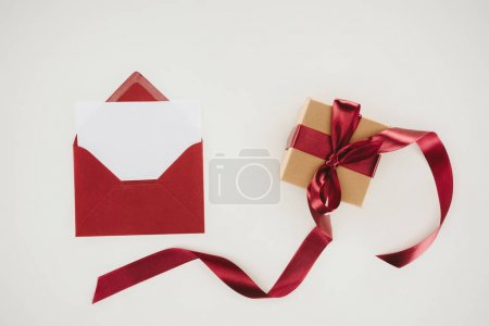 top view of red envelope with blank paper and gift box isolated on white