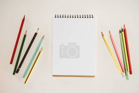 top view of blank notepad with colorful pencils isolated on white