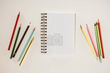 top view of blank notebook with colorful pencils isolated on white