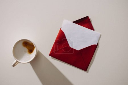 top view of red envelope with blank paper and cup of coffee