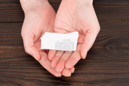 cropped shot of woman holding blank paper over wooden table