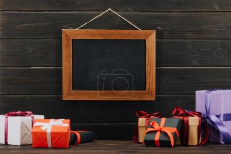 blank chalkboard in frame with gift boxes hanging on wooden wall