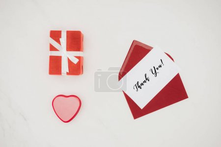top view composition of red envelope with thank you lettering on paper and gift boxes isolated on white