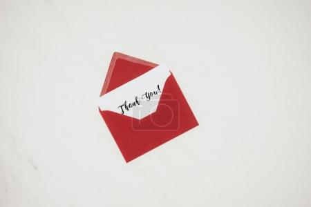 Photo for Top view of red envelope with THANK YOU lettering on paper isolated on white - Royalty Free Image
