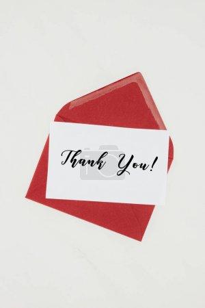 Photo pour Vue du dessus de l'enveloppe rouge avec le lettrage MERCI sur papier isolé sur blanc - image libre de droit